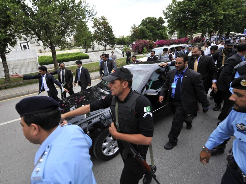 Security personnel escort Pak PM Yousuf Raza Gilani's car as he leaves the Supreme Court after a verdict in Islamabad. AFP Photo/Aamir Qureshi