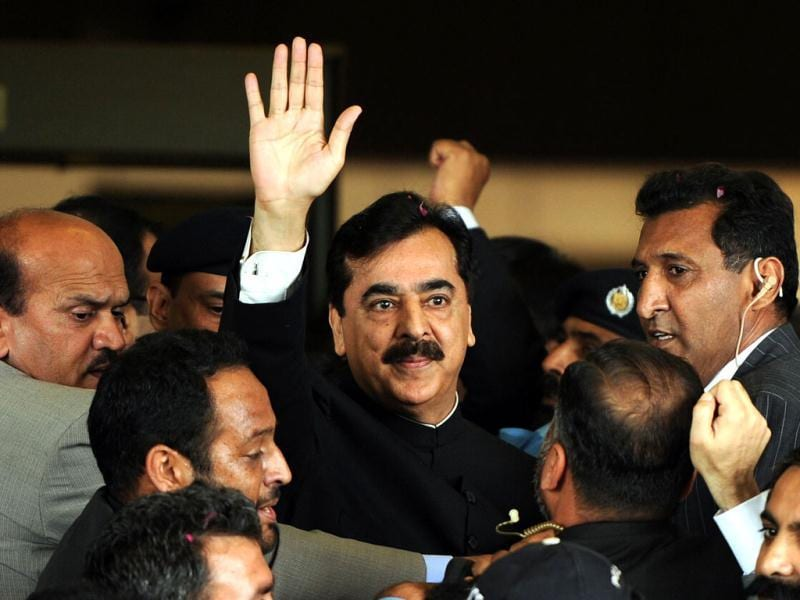 Pak PM Yousuf Raza Gilani is escorted by security as he waves upon his arrival at the Supreme Court building in Islamabad. AFP Photo/Aamir Qureshi