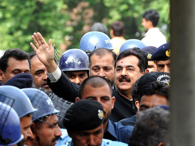 Pak PM Yousuf Raza Gilani is escorted by security as he waves upon his arrival at the Supreme Court building in Islamabad. Gilani was convicted of contempt of court by the country's highest court but avoided a jail term. AFP Photo/Aamir Qureshi
