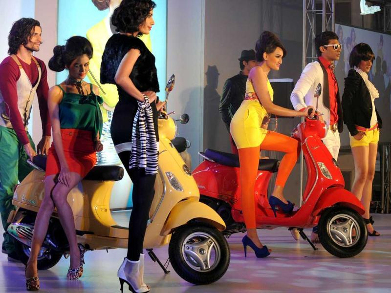 Models pose with Vespa scooters at the launch in Mumbai. AFP Photo/Indranil Mukherjee