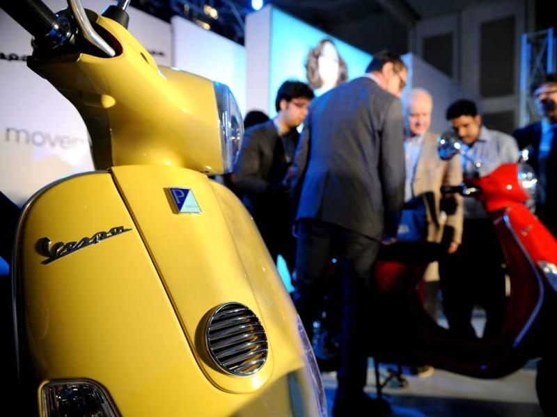 Piaggio officials and journalists inspect Vespa scooters after the launch in Mumbai. AFP Photo/Indranil Mukherjee