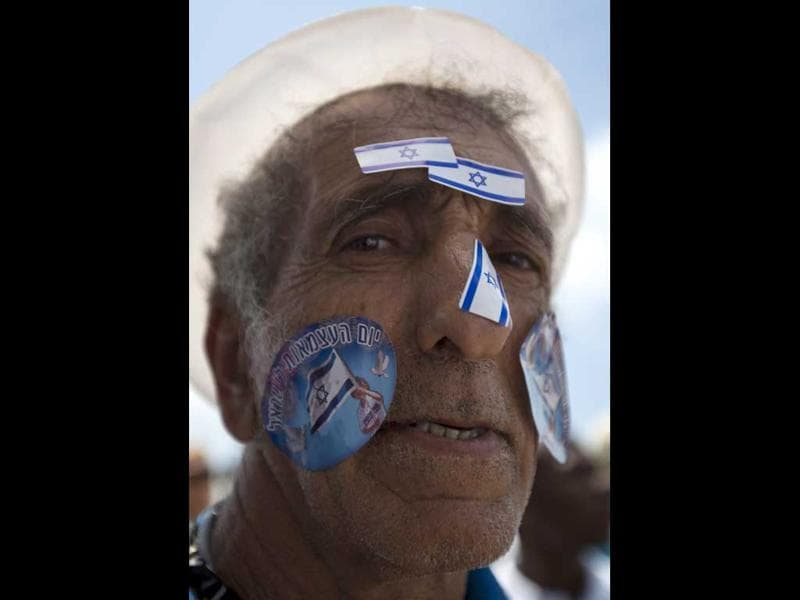 An Israeli man with stickers of the Israeli flag on his face during Israel's 64th Independence Day anniversary celebrations in Tel Aviv, Israel. AP Photo/Ariel Schali