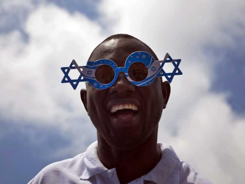 An African migrant worker cheers during Israel's 64th Independence Day anniversary celebrations in Tel Aviv, Israel, Thursday, April 26, 2012. AP Photo/Ariel Schalit