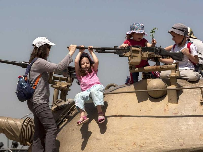 Israeli children play on top of an old military tank during a display by the army at the Armored Corps Museum as part of Independence Day celebrations in Latrun, near Jerusalem. Israel is celebrating its annual Independence Day, marking 64 years since the founding of the state in 1948. AP Photo/Sebastian Scheiner