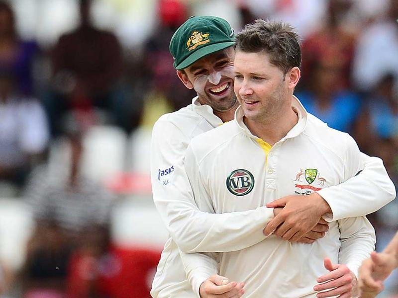 Australian captain Michael Clarke (R) is congratulated by Nathan Lyon after taking the wicket of West Indies batsman Ravi Rampaul during the fifth day of the third test match against West Indies in Roseau, Dominica. AFP Photo/Emmanuel Dunand