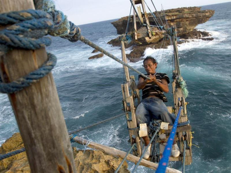 Fisherman Siswanto rides on a self-built wooden cable car, created by himself, to cross the sea at Timang beach in Gunung Kidul, near the ancient city of Yogyakarta. Reuters/Dwi Oblo