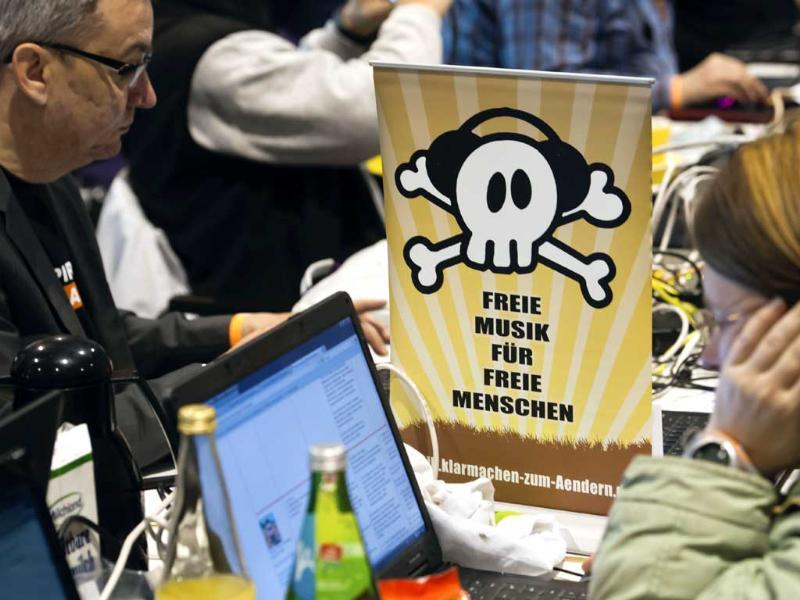 Members of the Pirate Party sit next to a poster reading