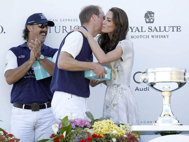 Catherine, the Duchess of Cambridge, kisses her husband, Britain's Prince William, while his teammate Santi Trotz (L) applauds as she presents awards following a polo match at the Santa Barbara Polo and Racquet Club for a charity event held in support of the American Friends of The Foundation of Prince William and Prince Harry in Santa Barbara, California. (Reuters/Phil McCarten)