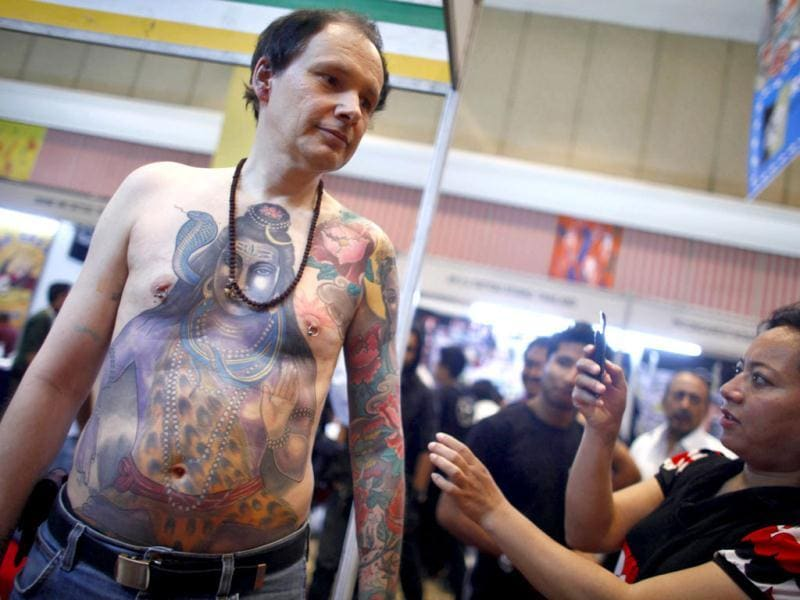 A Nepalese woman takes a picture of a foreign artist whose tattoo depicts Hindu God Shiva during the second International Tattoo Convention in Kathmandu. AP Photo/Niranjan Shrestha