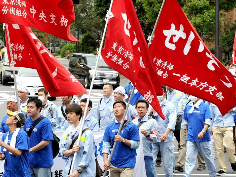People march on the street as they hold banners during a May Day demonstration on May 1, 2012. Several thousand people took part in the demonstration following a rally at a park. (AFP Photo)