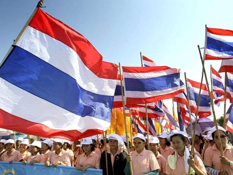 Workers demanding a wage increase carry Thai flags during a May Day rally in Bangkok. (AP Photo)