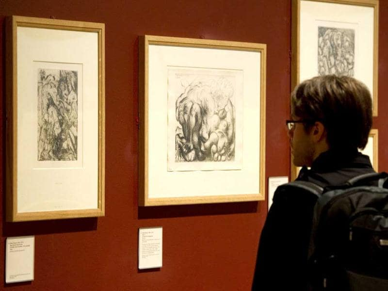 A man looks at two etchings entitled