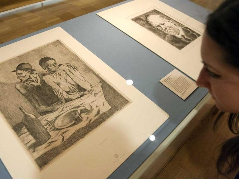 A person looks at an etching entitled