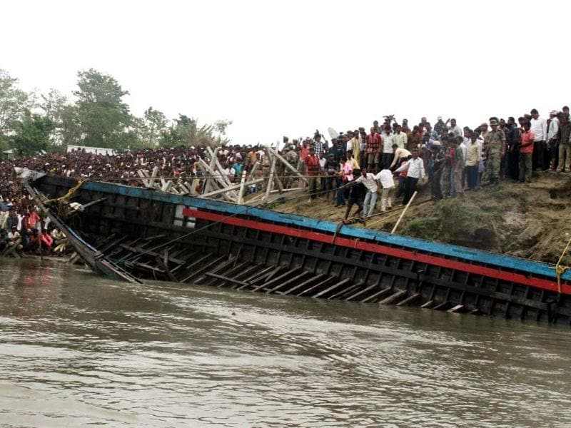 Villagers watch as a piece of a sunken ferry is pulled up onto the bank of the river Brahmaputra near Bura-Buri village in Goalpara district of Assam. AFP/Biju Boro