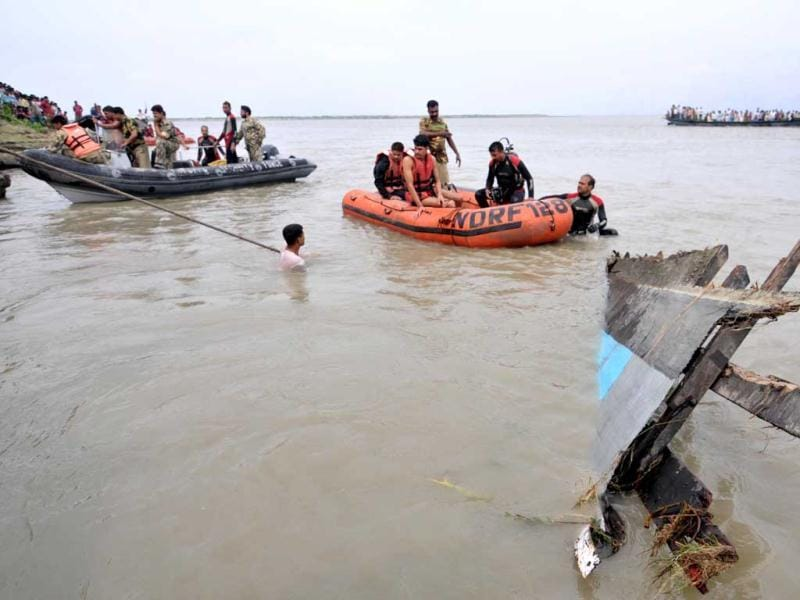 National Disaster Response Force (NDRF) personnel engage in the rescue operation of a sunken ferry near Bura-Buri village in Goalpara district of Assam. AFP/Biju Boro