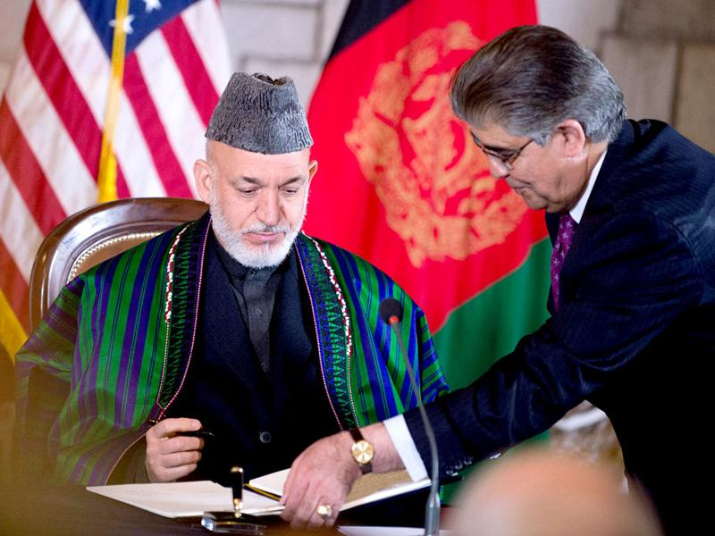 Afghan President Hamid Karzai signs the US-Afghanistan strategic partnership agreement on May 2, 2012 at the Presidential Palace in Kabul, Afghanistan. The agreement provides US military and financial support to Afghanistan for 10 years after the 2014 scheduled troop withdraw. AFP/Mandel Ngan