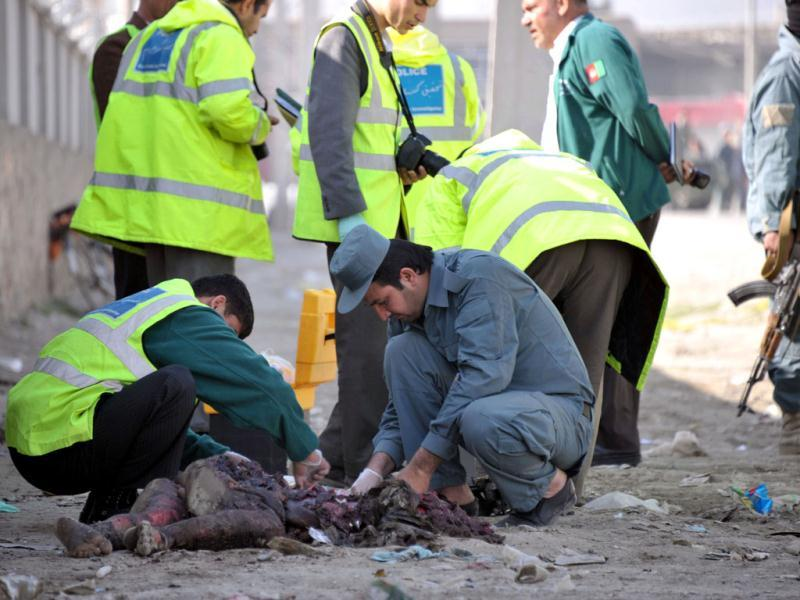 Afghan police check a dead body lying in front of a guesthouse in Kabul, after a suicide bomb attack. Taliban insurgents claimed a suicide attack in the Afghan capital Kabul, shortly after US President Barack Obama left the city after an overnight visit. (AFP Photo)
