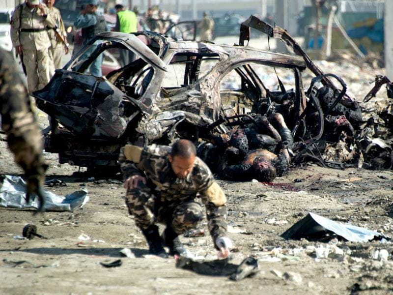An investigator looks at debris beside a charred vehicle containing a body at the site of a suicide bomb attack in Kabul. Taliban insurgents claimed a suicide attack in the Afghan capital Kabul, shortly after US President Barack Obama left the city after an overnight visit. (AFP Photo)