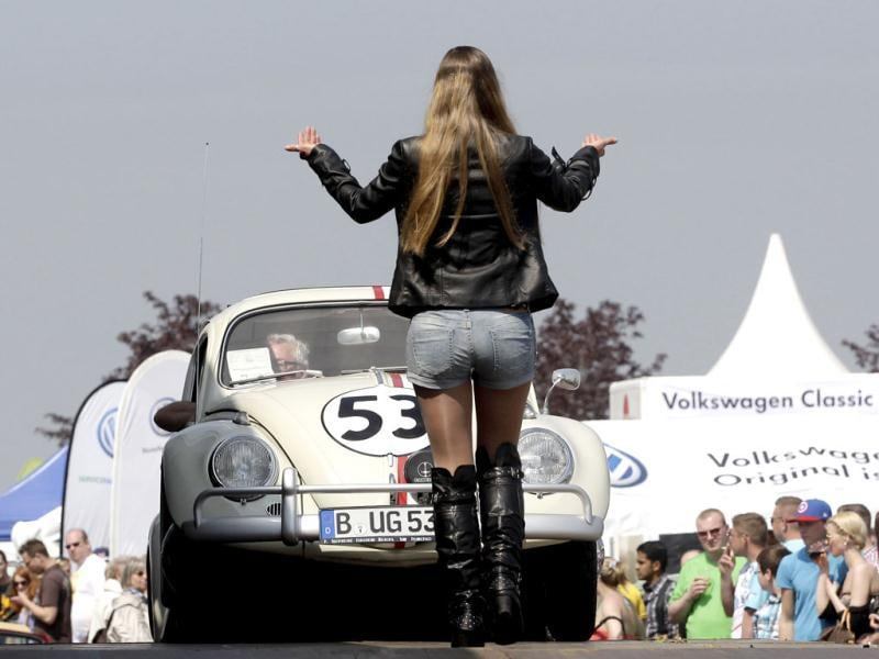 A volunteer directs a VW Beetle car to a presentation stage during the 29th annual