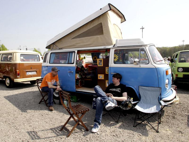 People sit outside a vintage Volkswagen van as they attend the 29th annual