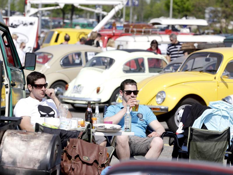 People sit in front of vintage Volkswagen Beetle cars during the 29th annual