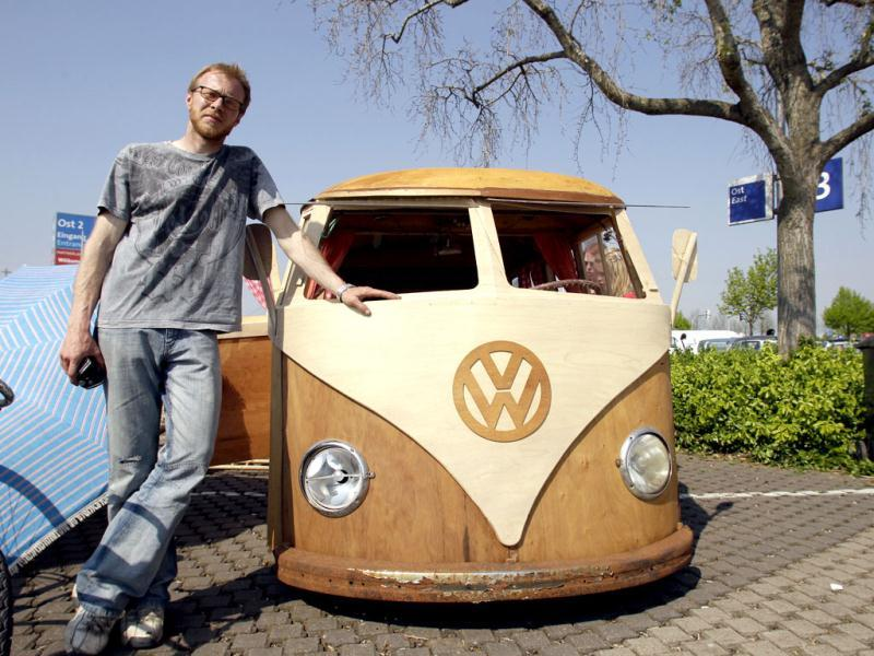 Martin Schuster, a 35 year old car salesman from Wuerzburg, poses next to his wooden VW T1 bus which he built himself at the 29th annual