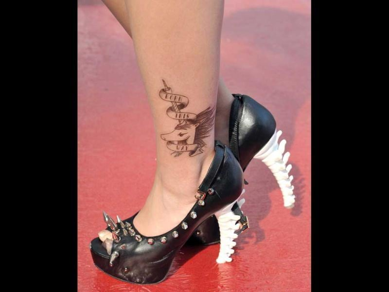 A fan of US pop diva Lady Gaga sports a pair of shoes and a tattoo similar to one her idole wears, as she poses before her concert in Hong Kong. AFP Photo/Laurent Fievet