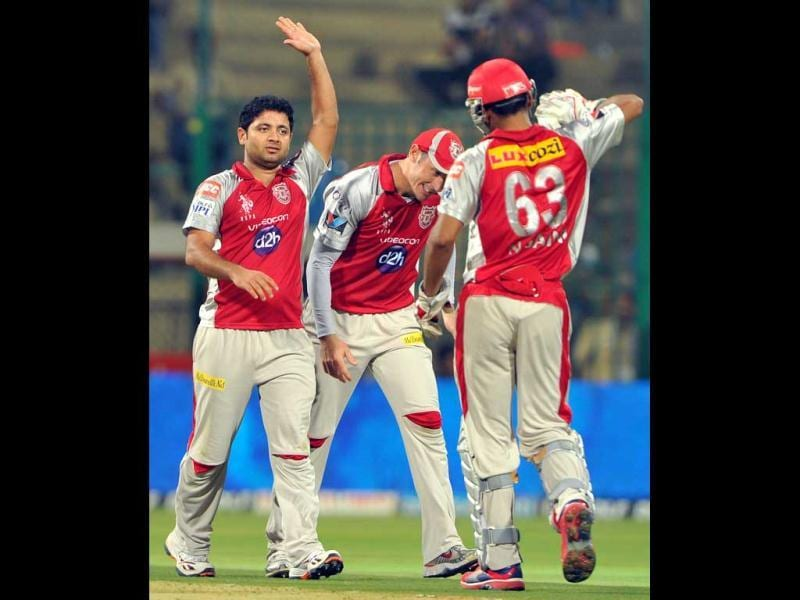 Kings XI Punjab bowler Piyush Chawla (L) celebrates the wicket of RCB batsman Virat Kohli (unseen) during the IPL Twenty20 cricket match between Royal Challenger Bangalore and Kings XI Punjab at the M. Chinnaswamy Stadium in Bangalore. AFP Photo/Manjunath Kiran