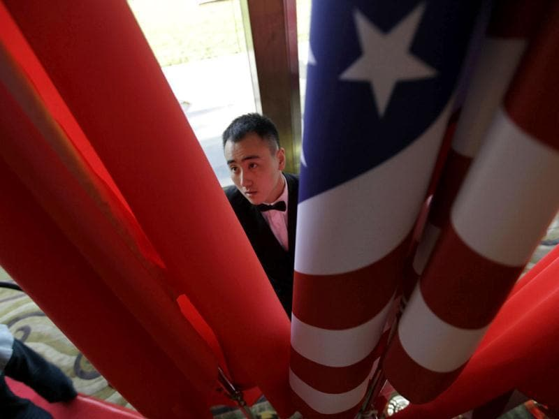 An attendant adjusts Chinese and American national flags ahead of the opening ceremony of US-China Strategic and Economic Dialogue at the Diaoyutai Guesthouse in Beijing. Reuters/Jason Lee