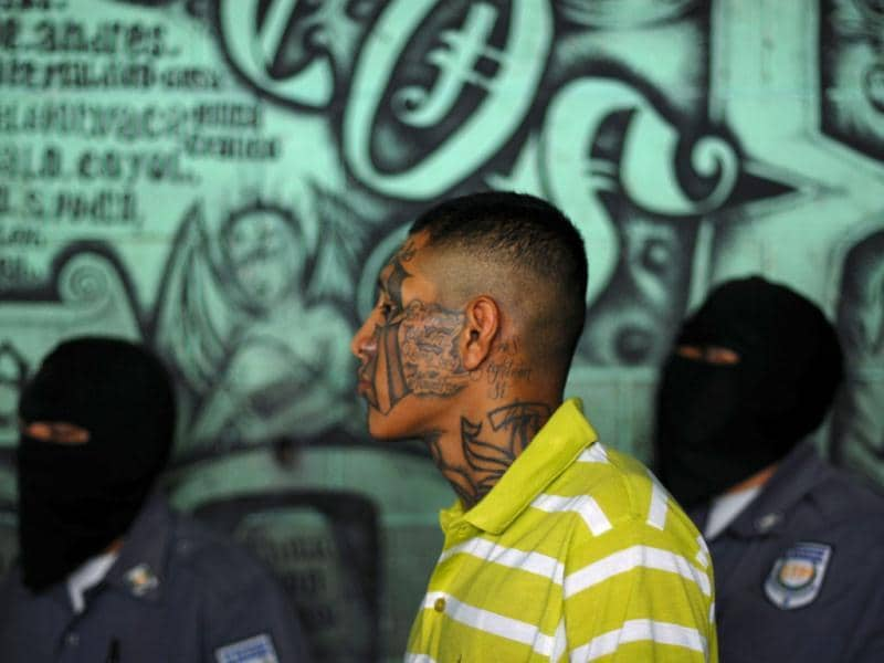 A gang member and inmate (C) stands near masked police officers inside the jail in Quetzaltepeque. Reuters/Ulises Rodriguez
