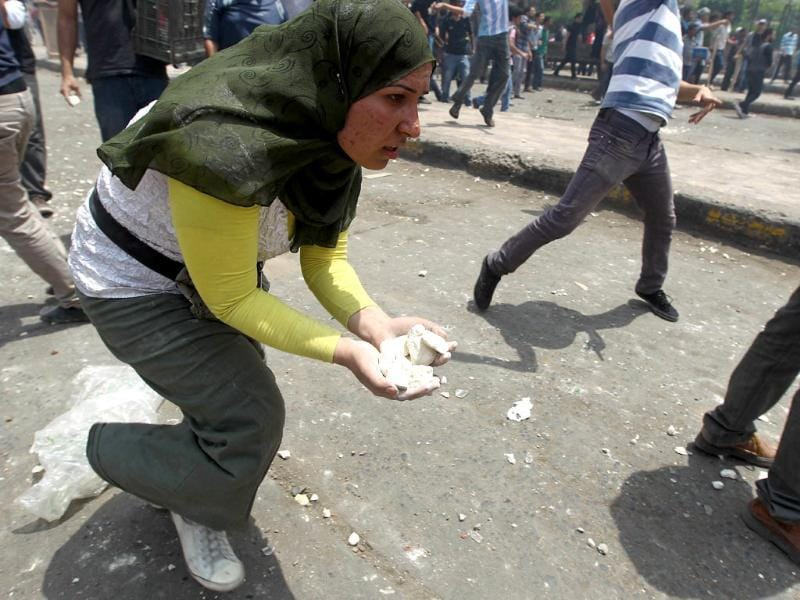 An Egyptian woman holds stones to give to anti-military protesters during clashes with unidentified attackers in the Abbassiya district of Cairo. Thugs attacked an anti-military protest near the defence ministry in Cairo and at least 20 people were killed, officials said, in the politically tense run-up to the first post-uprising presidential election. AFP PHOTO/KHALED DESOUKI