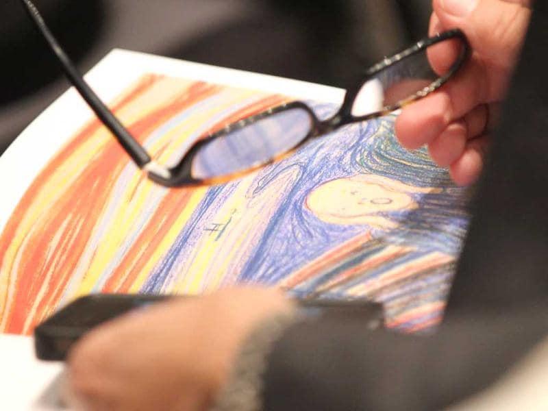 A person looks through a catalog as Edvard Munch's 'The Scream' is auctioned at Sotheby's May 2012 Sales of Impressionist, Modern and Contemporary Art in New York City. The masterpiece is one of four versions created by Munch and the only one that is privately owned. Mario Tama/Getty Images/AFP
