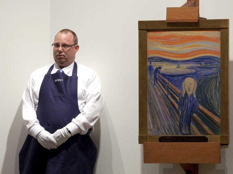 An employee stands next to 'The Scream' painted by Edvard Munch at a Sotheby's auction in New York. The masterpiece is one of four versions created by Munch. Reuters/Andrew Burton