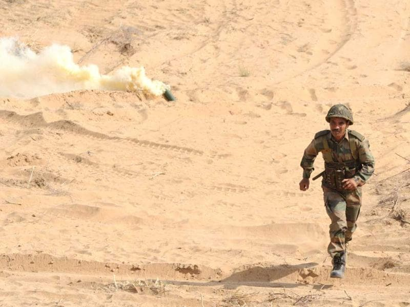 A soldier heads back after lighing a smoke canister during the Shoor Veer military exercise. AFP/Sam Panthaky