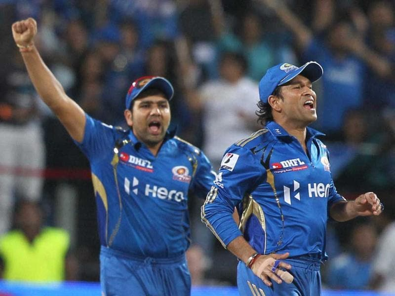 Mumbai Indians Rohit Sharma and Sachin Tendulkar celebrate the dismissal of Pune Warriors batsman Michael Clarke during their IPL 5 match in Pune. PTI Photo/Shirish Shete