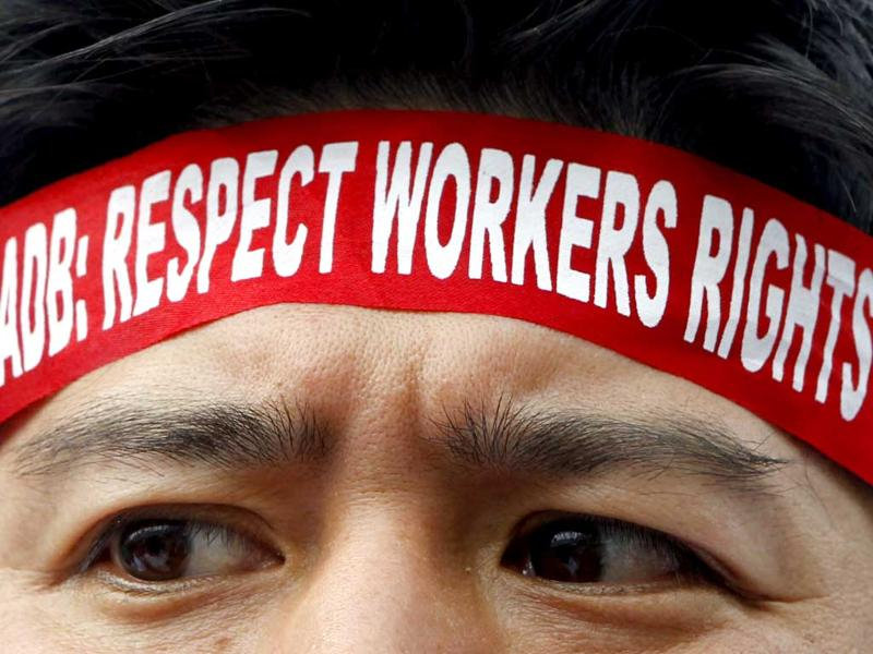 A foreign delegate wearing a headband tries to enter the Philippine International Convention Center (PICC) during a protest on the third day of the Asian Development Bank (ADB) 45th Annual Board of Governors meeting in Manila. REUTERS/Erik De Castro