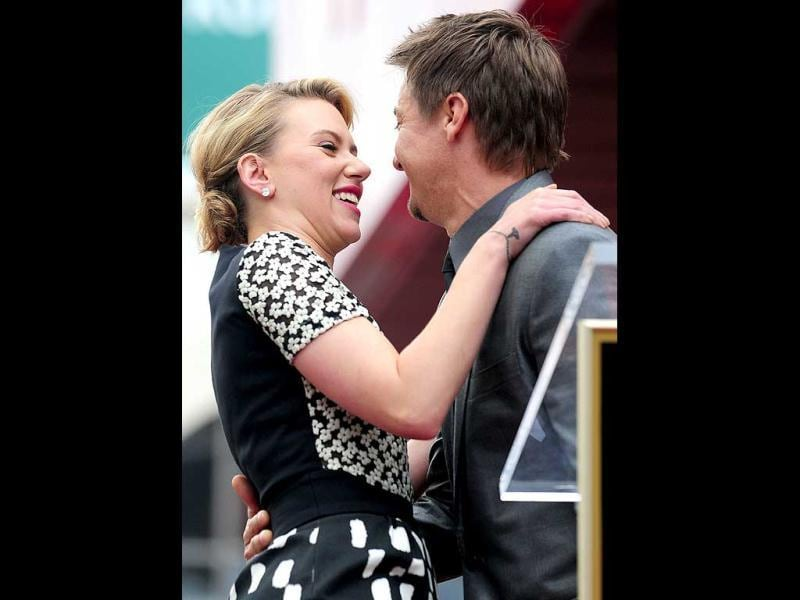 Renner planted a big kiss on Johansson's cheek as she knelt down by the California landmark.