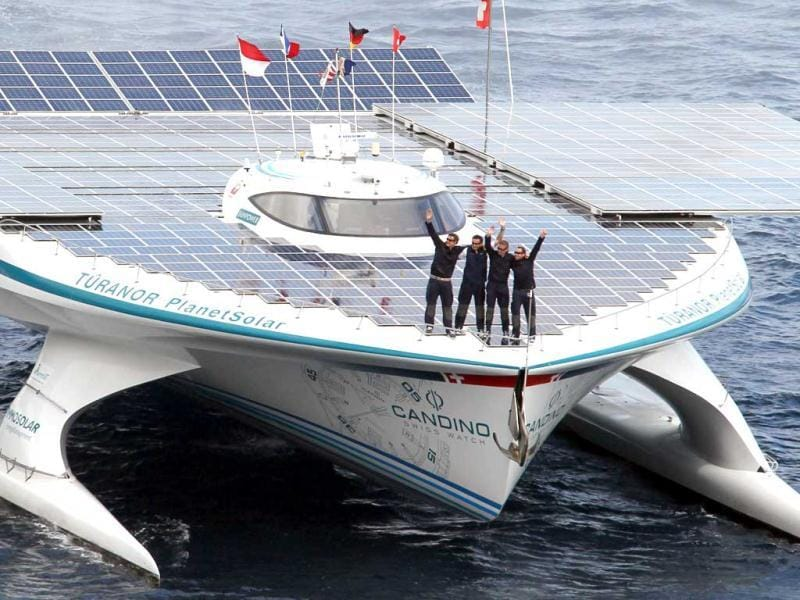 Team members of PlanetSolar wave as they achieve the first around-the-world tour with only solar energy in Monaco. The biggest solar boat ever built progressed through Atlantic Sea, Panama canal, Pacific Ocean and is back to Mediterranean Sea through Suez Canal. AFP Photo/Valery Hache