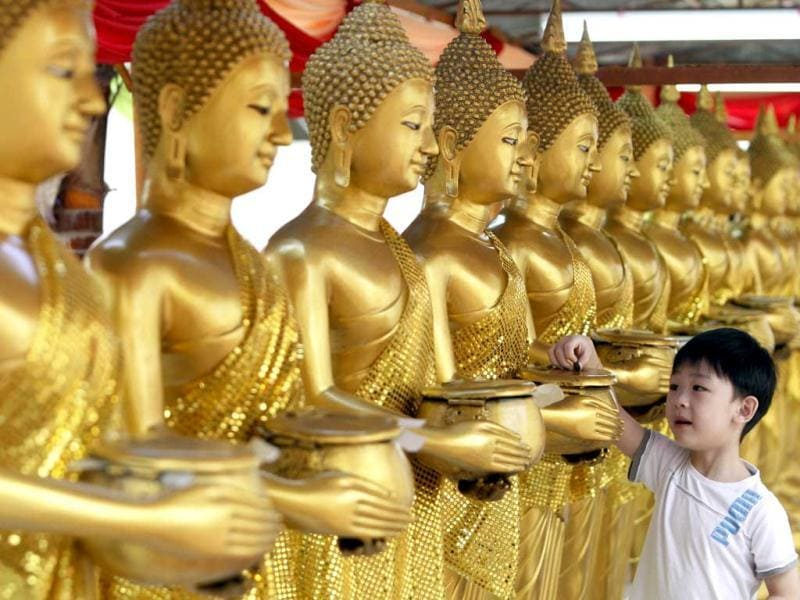A boy drops coins into golden Buddha statues as a symbol of blessing during Wesak Day, known as Buddha's birthday, at Thai Buddhist Chetawan Temple, Malaysia. AP Photo/Lai Seng Sin