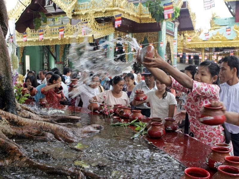 A woman pours water to Bo-tree as the followers pay a visit to Myanmar's fame Shwedagon Pagoda on the full-moon day of Kasone, the second month of Myanmar Calendar, in Yangon, Myanmar. (AP Photo/Khin Maung Win)