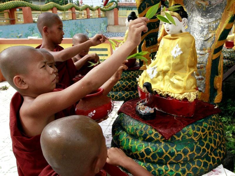 Myanmar's Buddhist novice monks sprinkle waters to a statue of Buddha as a traditional rite on the full-moon day of Kasone, the second month of Myanmar Calendar, at Potataung Pagoda in Yangon, Myanmar. (AP Photo/Khin Maung Win)