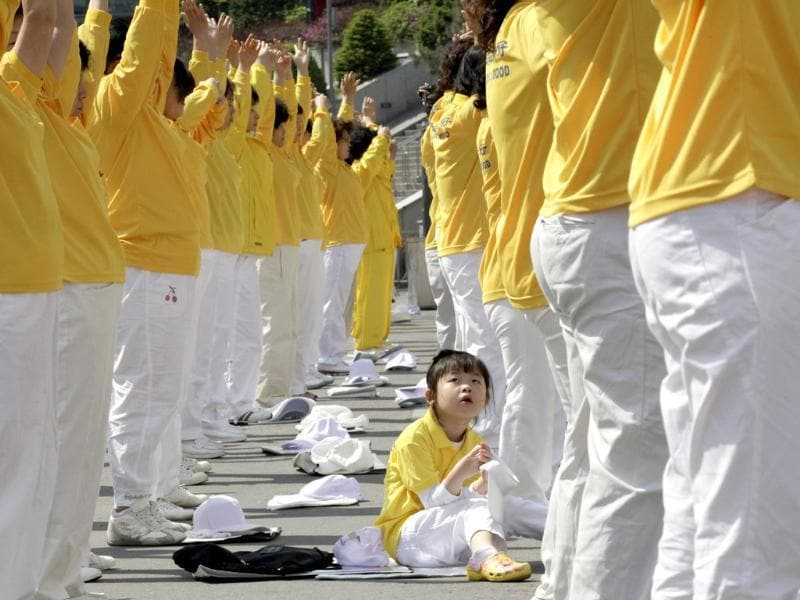 South Korean members of Falun Dafa, also known as Falun Gong, perform as Um Chae-yeon, a daughter of a member, looks on during a rally to commemorate World Falun Dafa Day, which will be officially celebrated on May 13, in Seoul, South Korea. AP Photo/Ahn Young-joon