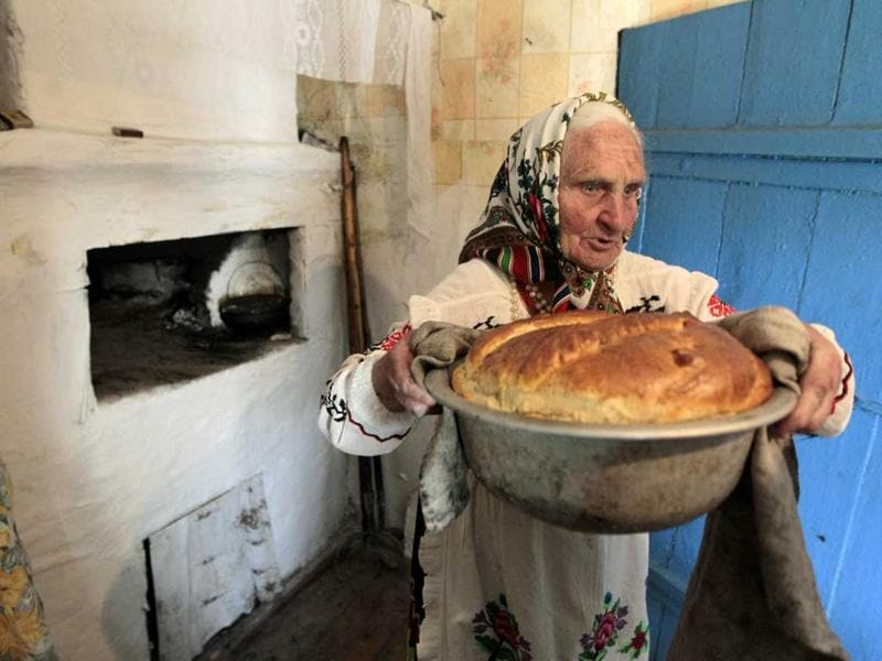A woman in national dress bakes bread to prepare for a ritual celebrating the pagan god Yurya in the village of Pogost, some 250 km (155 miles) south of Minsk. Locals believe that Yurya protects their harvest, and the annual tradition on May 6 is devoted to praying for plentiful future harvests. REUTERS/Vasily Fedosenko