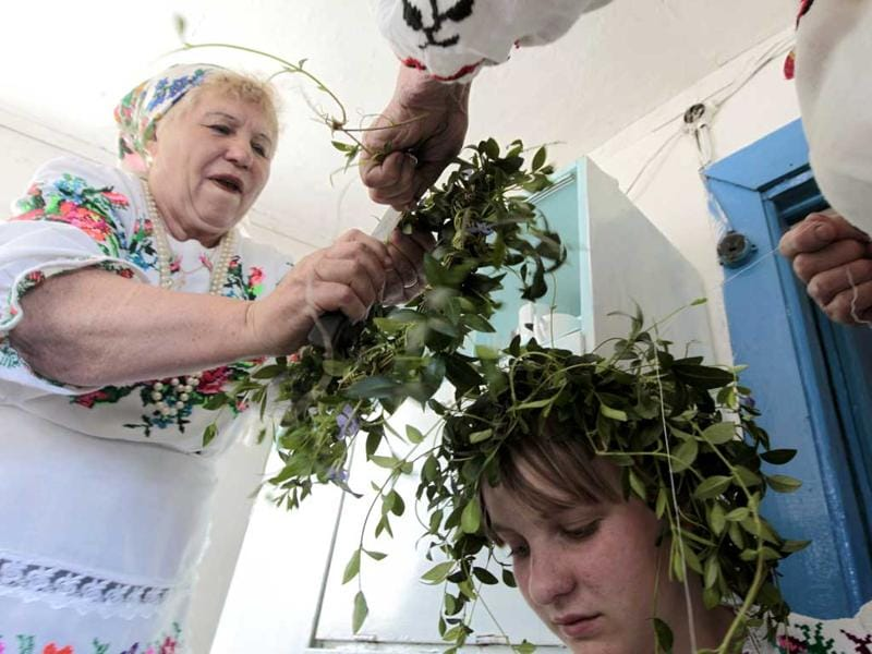 Women in national dresses place wreaths made of periwinkle leaves on a girl's head to prepare for a ritual celebrating the pagan god Yurya in the village of Pogost. REUTERS/Vasily Fedosenko