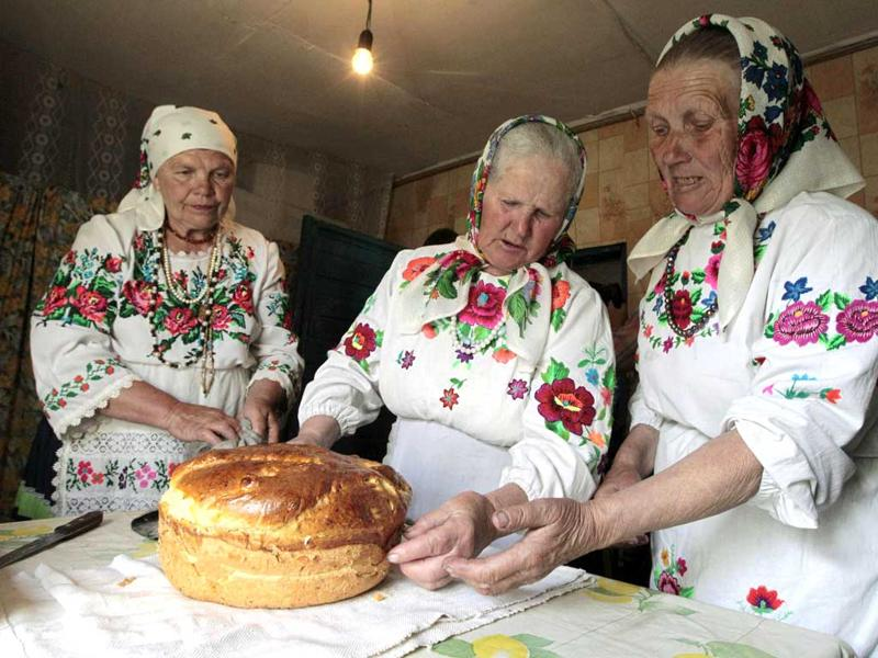 Women in traditional clothes bake bread to prepare for a ritual celebrating the pagan god Yurya in the village of Pogost, some 250 km (155 miles) south of Minsk, May 5, 2012. Locals believe that Yurya protects their harvest, and the annual tradition on May 6 is devoted to praying for plentiful future harvests. REUTERS/Vasily Fedosenko