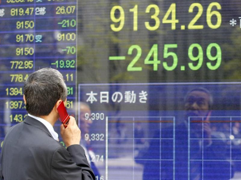 A man speaks on a mobile phone in front of a securities firm's electronic stock board in Tokyo. Asian stock markets were pummeled by weekend election results in Greece and France that heightened uncertainty about Europe's ability to solve its debt crisis. AP Photo/Shizuo Kambayashi
