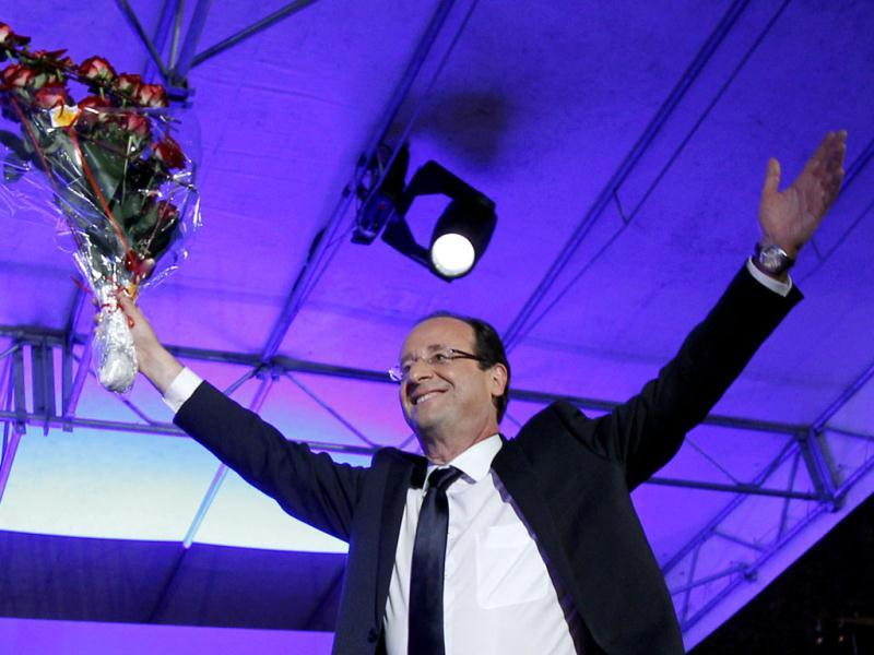 President-elect Francois Hollande holds a bouquet of roses after delivering his speech in Tulle, central France. Hollande defeated Nicolas Sarkozy to become France's next president. Sarkozy conceded defeat minutes after the polls closed. AP Photo/Christophe Ena