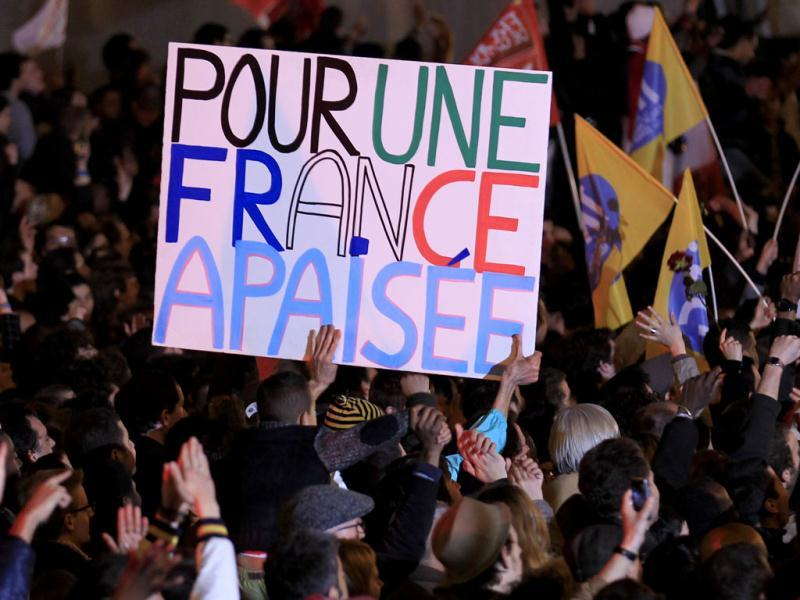 Supporters of France's newly-elected President Francois Hollande celebrate during a victory rally at Place de la Bastille in Paris. France voted in elections on Sunday and Francois Hollande becomes the nation's first Socialist president in 17 years. The slogan reads