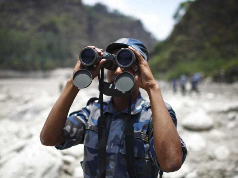 A member of the rescue team of the Nepalese police looks through a pair of binoculars around the site which used to be a small village, swept away by a flash flood caused by an avalanche in the Annapurna mountain range on Saturday, in Kaski district. At least 19 people, including three foreigners, are confirmed to have died and 45 still missing till today due to the flood in Pokhara and adjoining villages in Kaski district, according to a local media report. (Reuters)