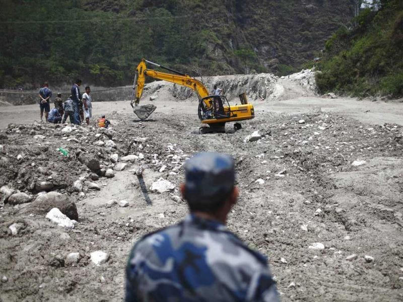 Members of a rescue team dig with the help of a excavator at a site that used to be a small village, swept away by a flash flood caused by an avalanche in the Annapurna mountain range on Saturday, in Kaski district. At least 19 people, including three foreigners, are confirmed to have died and 45 still missing till today due to the flood in Pokhara and adjoining villages in Kaski district, according to local media report. (Reuters)
